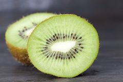 Halves of kiwi fruit. A green heart and halves of kiwi fruit with seeds, closeup stock image
