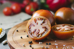 Halves of Kumato tomatoes on wooden board surrounded by vegetables and spices. Halves of Kumato tomatoes on wooden board surrounded by vegetables and spices royalty free stock photos
