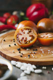 Halves of Kumato tomatoes on wooden board surrounded by vegetables and spices. Halves of Kumato tomatoes on wooden board surrounded by vegetables and spices royalty free stock image