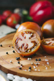 Halves of Kumato tomatoes on wooden board surrounded by vegetables and spices. Halves of Kumato tomatoes on wooden board surrounded by vegetables and spices royalty free stock photography