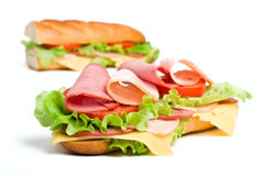 Halves of long baguette sandwich. Two halves of long baguette sandwich with lettuce, tomatoes, ham, turkey breast and cheese Stock Photo