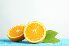 Halves orange with leaves on blue table against white background. Space for text stock photos
