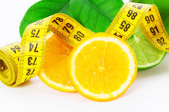 Halves of an orange and lime with measuring tape on a white background Royalty Free Stock Images