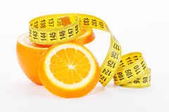 Halves of an orange with measuring tape on a white background Royalty Free Stock Photography