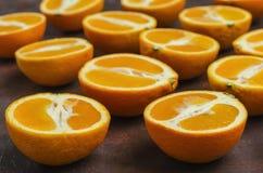 Halves of oranges on a dark. Halves of oranges on a dark brown background stock photo