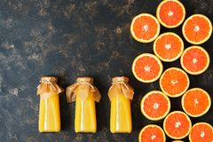Halves of oranges and juice in bottles on a dark background. Orange juice in bottles lying on the surface. Copy space. royalty free stock photos
