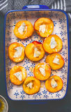 Halves of peaches in baking dish with cheese and honey, top view, close up. Stock Images