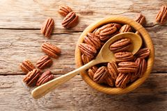 Halves of pecans in a bowl on a wooden table. horizontal top view, rustic. Halves of pecans in a bowl on a wooden table. horizontal top view from above, rustic royalty free stock image