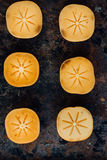 Halves of persimmon fruit on black metal surface. Halves of persimmon fruit on black metal surface royalty free stock images