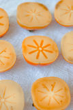 Halves of persimmon fruit on fabric material. Halves of persimmon fruit on fabric material royalty free stock photos