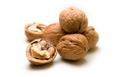 Halves and a pile of walnuts on a white background focus on half Royalty Free Stock Photography