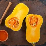 Halves of raw organic butternut squash on baking pan with honey. Selective focus. Square picture. Rustic style royalty free stock images