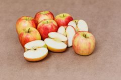 Halves of red apples on a brown background. Harvest royalty free stock photography