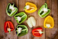 Halves of red, green, black, white and yellow bell peppers. On wooden background Royalty Free Stock Images
