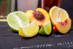 Halves and slices of lemon. peach and lime on a dark wooden textured background. Lemon in focus. Shallow depth of field. Royalty Free Stock Photos