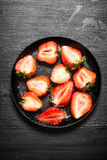 Halves of strawberry in the old plate. Stock Photo