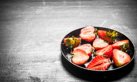 Halves of strawberry in the old plate. Stock Photos