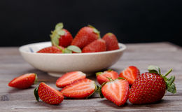 Halves of strawberry. Ripe strawberries in a ceramic bowl on a wooden background royalty free stock images