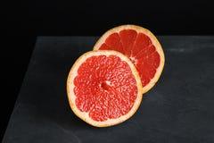 Halves of tasty ripe grapefruit on black. Background stock images