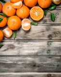 Halves and whole mandarins. On wooden background stock images