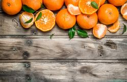 Halves and whole mandarins. On wooden background royalty free stock photo