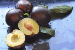 Halves and whole plums on a dark shiny background Royalty Free Stock Photos