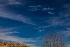 Halvmåne som omges av vita cirrusmolnmoln och blå himmel arkivbilder