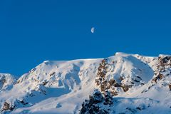 Halvmåne som stiger över schweiziska fjällängar royaltyfri foto