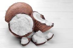 Halvor av kokosnöten med kokosnötshavings och små stycken av kokosnöten på en vit bakgrund royaltyfri bild