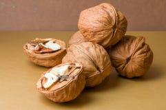 Halvor och en hög av valnötter på en brun bakgrund Royaltyfria Foton