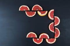 Halvs cortados del pomelo rojo en negro con el espacio de la copia Imagen de archivo