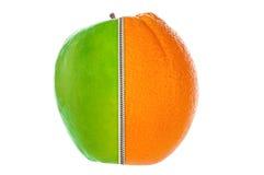 Halvt äpple och apelsin som sammanfogas av blixtlåset royaltyfria foton