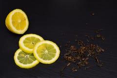 Halvt och skivor av den mogna citronen, kritiserar torra teblad på svart boaen arkivbilder