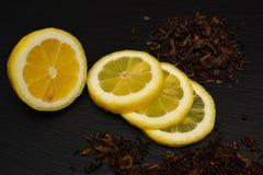 Halvt och skivor av den mogna citronen, kritiserar torra teblad på svart boaen royaltyfria foton