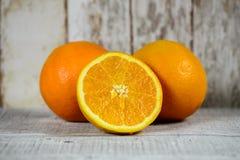 Halvt orange och två apelsiner Arkivfoto