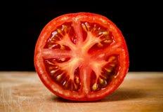 Halvt snitt som skivas av den nya tomaten på den Wood tabellen Royaltyfri Foto