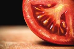 Halvt snitt som skivas av den nya tomaten på den Wood tabellen Royaltyfria Foton