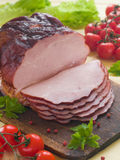 Ham. Whole ham with tomato in the background, selective focus Stock Photos