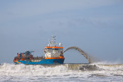 HAM 311 front rainbowing. A trailing suction hopper dredger rainbowing royalty free stock photos