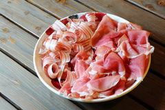 Ham and bacon. A dish with ham and raw bacon on a rough table Royalty Free Stock Image