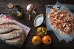 Ham with bread, tomato, garlic and olive oil stock images