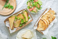 Ham bread with vegetable salad and tomato on a table and paper royalty free stock photos