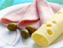 Ham and cheese. Slices of yellow cheese and ham on plate royalty free stock photo