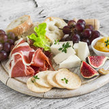 Ham, cheese, grapes, figs, nuts, bread ciabatta, cracker, jam on white wooden board on bright wooden surface. Rustic style. Appetizer to wine royalty free stock images