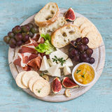 Ham, cheese, grapes, figs, nuts, bread ciabatta, cracker, jam on white wooden board  on bright wooden surface. Stock Photos