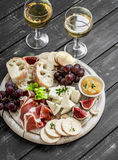 Ham, cheese, grapes, figs, nuts, bread ciabatta, cracker, jam on white wooden board on bright wooden surface. Rustic style. Stock Photography