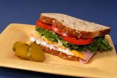 Ham, cheese, lettuce and tomato sandwich with pickles Royalty Free Stock Image