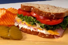 Ham, cheese, lettuce and tomato sandwich with pickles and chips Stock Images
