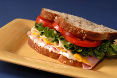 Ham, cheese, lettuce and tomato sandwich on yellow plate Royalty Free Stock Photography