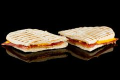 HAM AND CHEESE PANINI with reflection  on black background stock photos